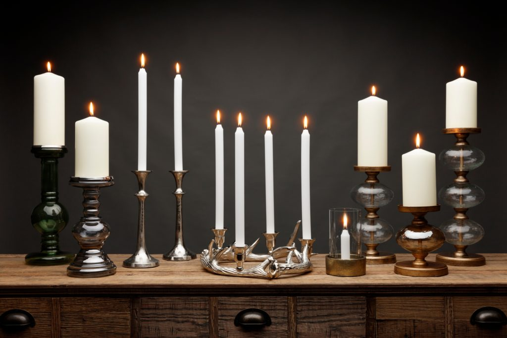 Grouping of Various Candles in Mix of Candle Holders on Wood Table