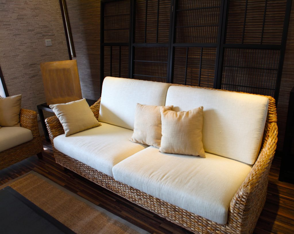 Natural Toned Wicker Couch with Beige Cushions and Throw Pillows