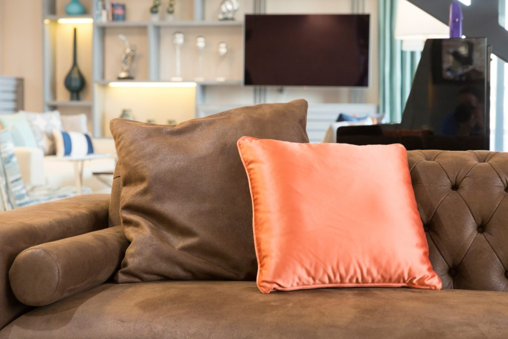 Pair of Silken Peachy Hued Pillows with Dark Toffee-Brown Velvet Couch in a Contemporary Design Thats Gorgeous
