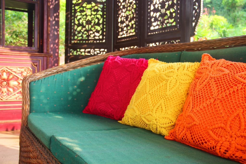 Breezy Wicker Outdoor Sofa with Jade Cushions Complement the Vivid Boldly Colored Lacy Throw Pillows