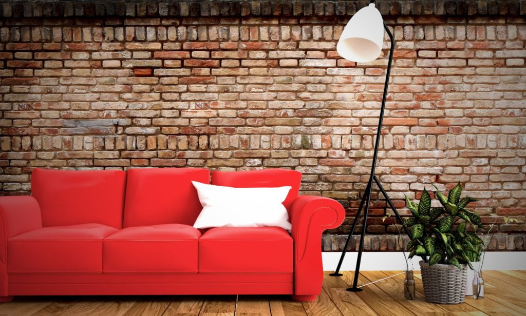 Bright Red Couch with White Pillow Against Rustic Brick Wall