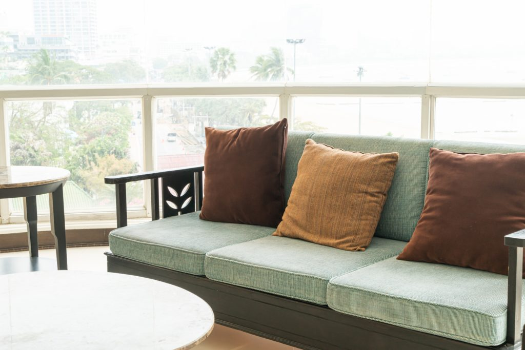 Contemporary Sea-Foam Green Couch Features a Dark-Wood Simplistic Frame Highlighted with Two Earthy-Brown Pillows & One Tan-Gold Pillow