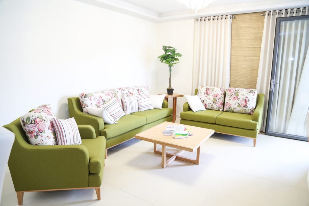 Elegant Spring-Green Couch Is Paired with Fresh Floral Back Pillows in Rose-Pink & Ivory-Cream with Smaller Striped Throw Pillows