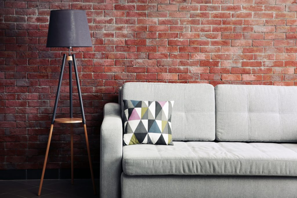 Gray Couch with Colorful Pillow Against Rustic Brick Wall