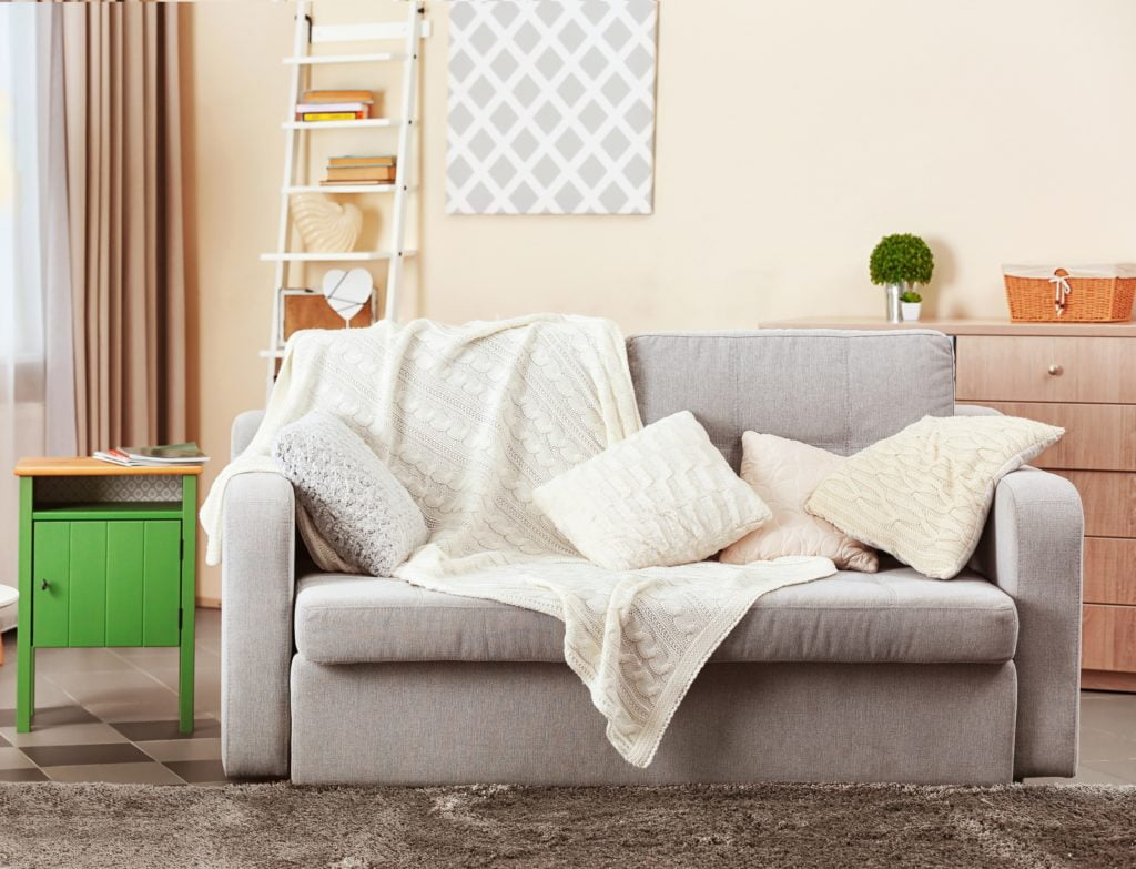 Gray Couch with White Coverlet and Pillows in Bright Modern Room