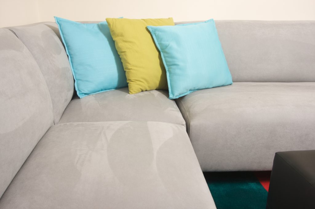 Gray Suede Couch with Gold and Aqua Throw Pillows