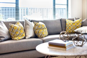 Large Gray Corner Couch with Yellow and Gray Throw Pillows