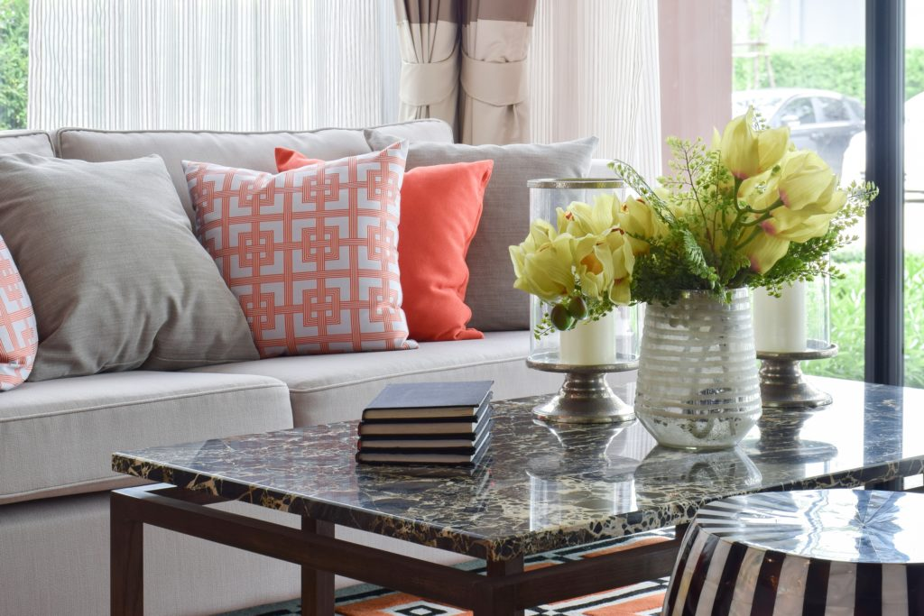 Light Gray Couch with Colorful Pillow Cluster and Marble top Table
