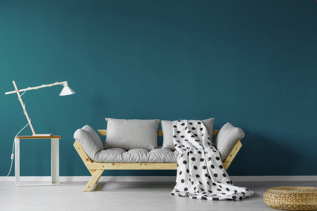 Light Gray Futon Couch with Matching Gray Pillows Against Teal Wall