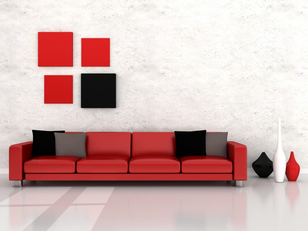 Long Red Couch with Dark Pillows Against Textured White Wall
