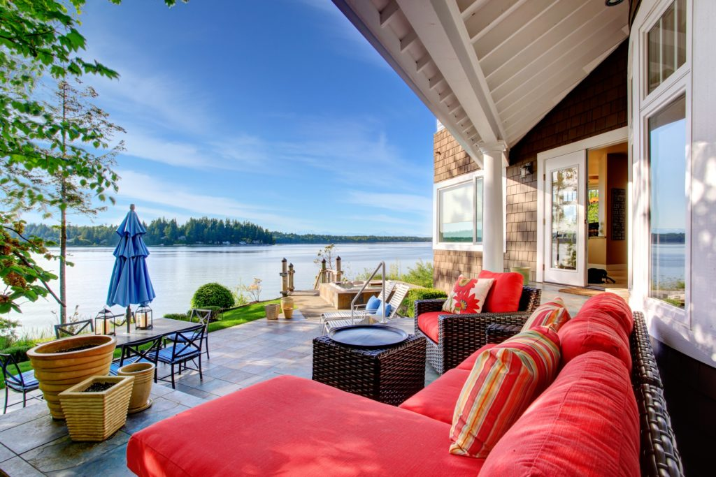 Luxury Outdoor Patio Waterside Room with Red Couch and Colorful Pillows