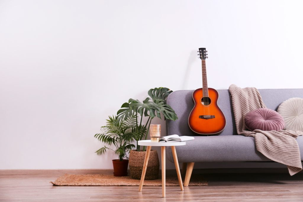 Minimalist Gray Couch with Acoustic Guitar and Decorative Round Pillows
