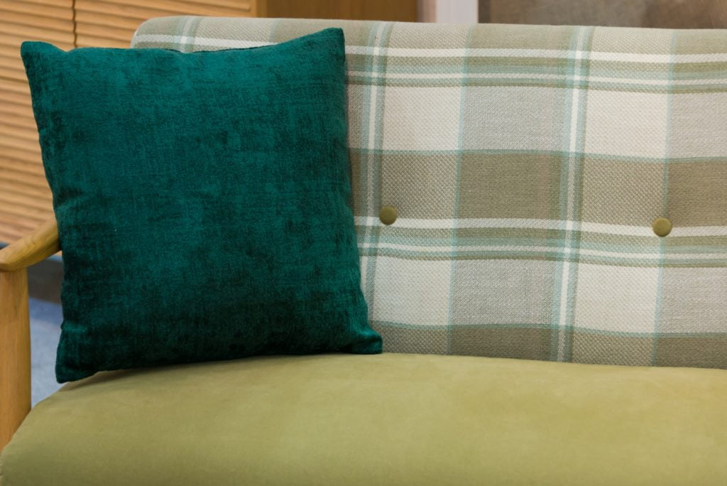 Refined Dark Pine Green Fabric Pillow On a Covered Contemporary Couch with Pale Olive Seat Plaid Back Design