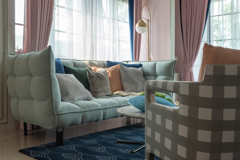 Soft Charming Mint Green Couch Featuring a Variety of Pastel Throw Pillows