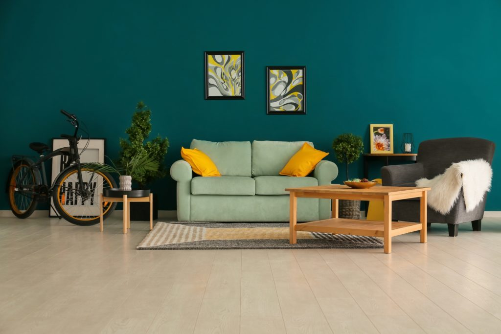 Stunning Dark Teal Wall Is Anchored by a Silvery Soft Pale Green Sofa Accented with Two Bright Golden Yellow Pillows