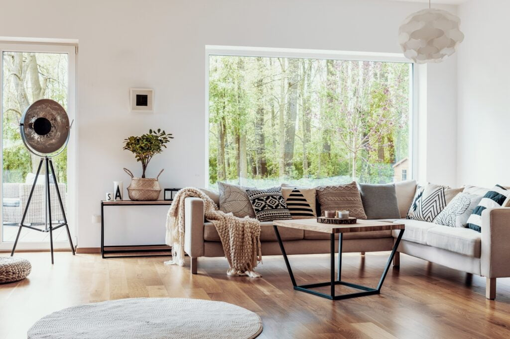 Beige Sectional Corner Sofa and Round Rug in Living Room with Scenic View