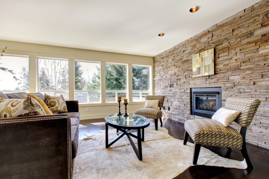 Bright Country Style Living Room with Brown Couch and Stone Wall