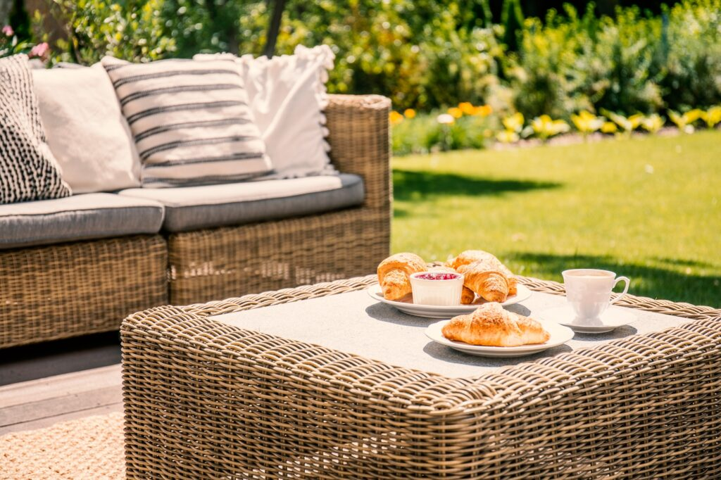 Charming Outdoor Deck Setting with Beige Wicker Settee and Table with Natural Fiber Rug
