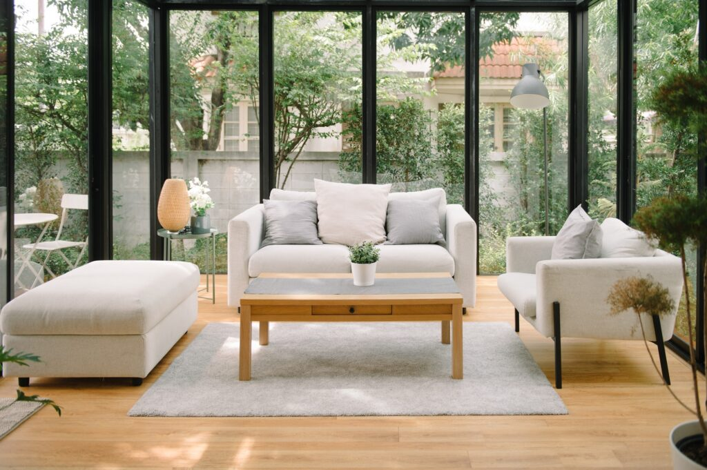 Elegant Gray Sofa with Matching Parlor Chair and Ottoman in Glass Walled Solarium
