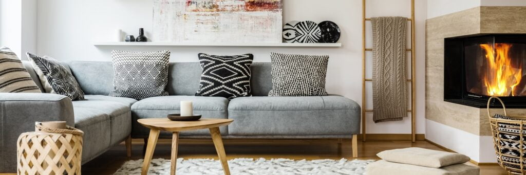 Gray Den Corner Sectional Sofa with Textured Gray and White Rug and Fireplace