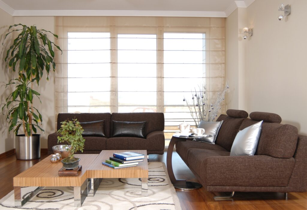 Living Room with Two Brown Couches and Geometric Rug Design