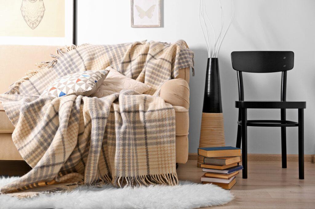 Retro Beige Sofa with Plaid Blanket and Fluffy White Shag Rug