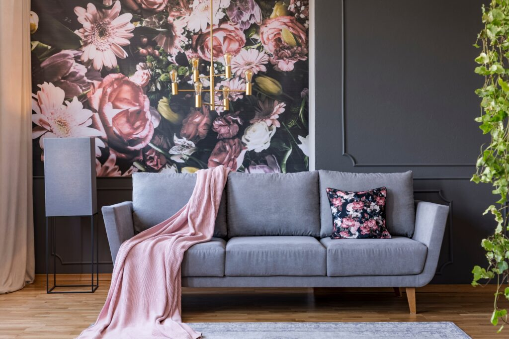 Retro Gray Couch with Powder Pink Blanket Enhanced by Stunning Floral Wallpaper