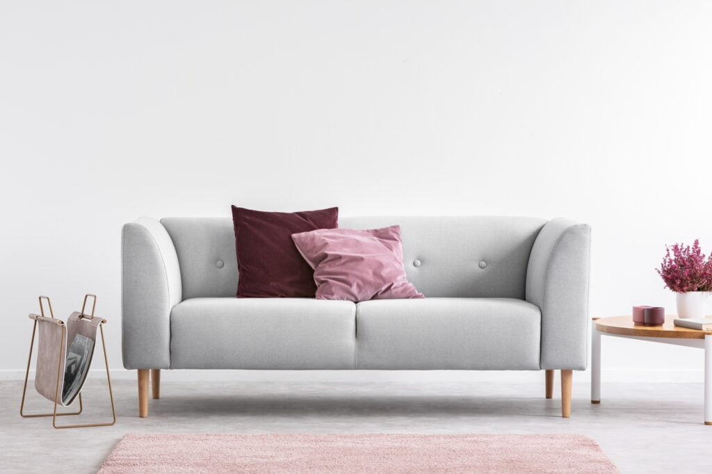 Unique Living Room Decor with Gray Settee and Colorful Pillows with Pale Lilac Rug