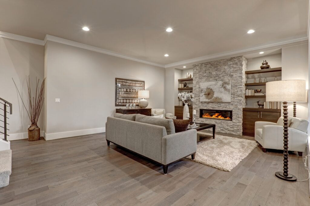 Warm Den Interior Featuring Gray Sofa with Stone Fireplace and Light Beige Rug
