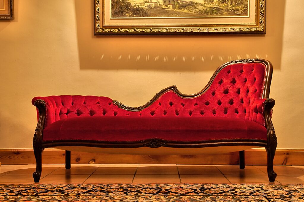 Charming Antique Red Living Room Settee Beneath Classic Painting