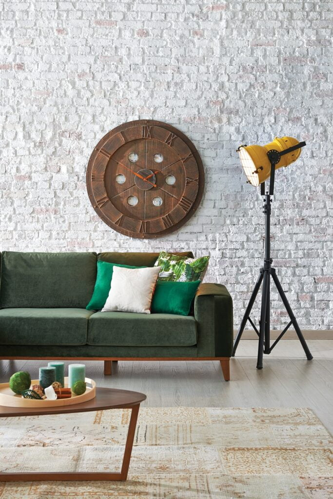 Modern Boho Den with Green Sofa Stone Wall and Vintage Rug
